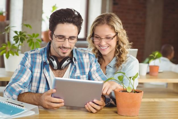 Glückliche geschäftsleute, die digitale tablette im kreativen büro betrachten