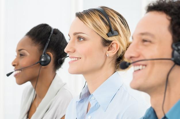 Glückliche geschäftsleute, die headsets tragen, die im call center arbeiten
