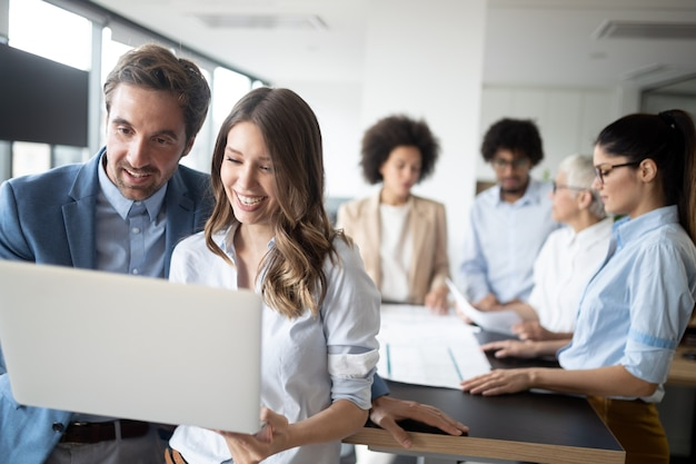 Glückliche geschäftsleute, die im büro arbeiten und brainstormen