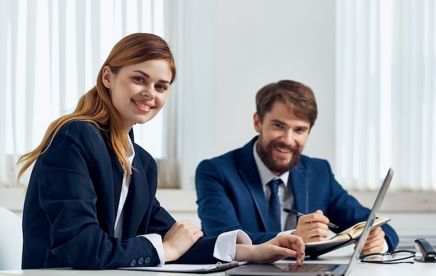Glückliche geschäftsleute im büro mit einem laptop sitzen am tisch in einem hellen raum