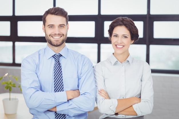 Glückliche geschäftsleute mit den armen kreuzten im büro