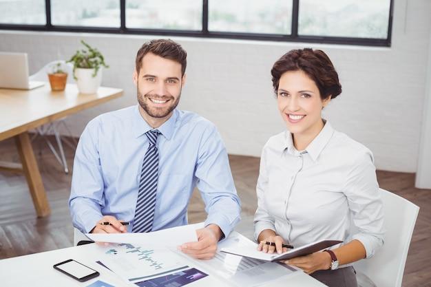 Glückliche geschäftsleute mit den dokumenten, die im büro sitzen