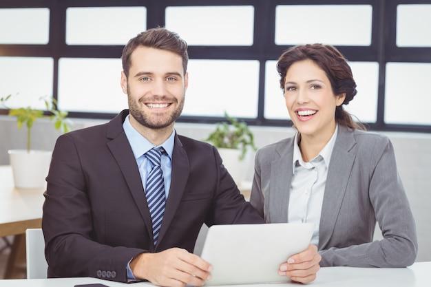 Glückliche geschäftsleute mit digitaler tablette im büro