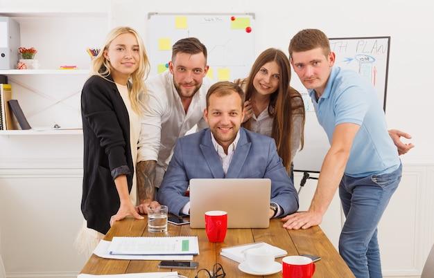 Glückliche geschäftsleute team zusammen in der nähe von laptop im büro