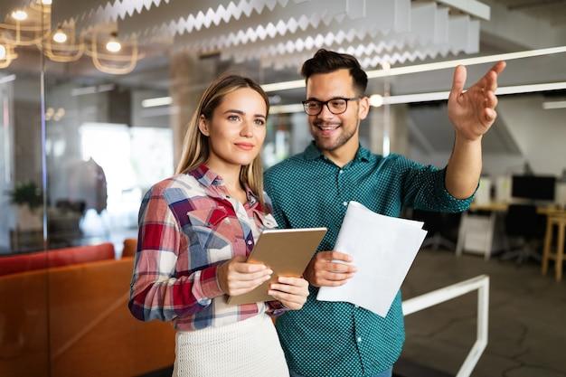 Glückliche geschäftspartner. kollegen diskutieren über geschäfte und lächeln, während sie durch den bürokorridor gehen
