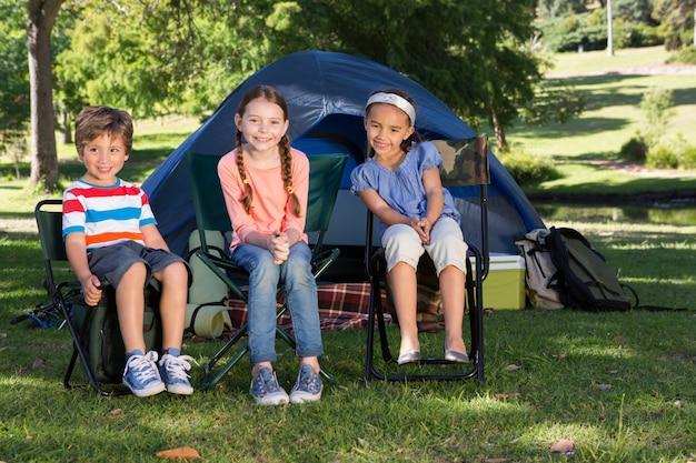 Glückliche geschwister auf einem camping-ausflug an einem sonnigen tag