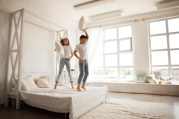 Glückliche geschwister, die auf bett im schlafzimmer springen