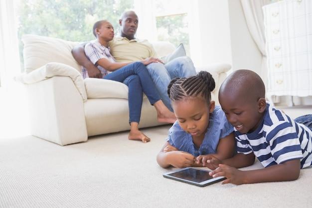 Glückliche geschwister, die digitale tablette verwenden