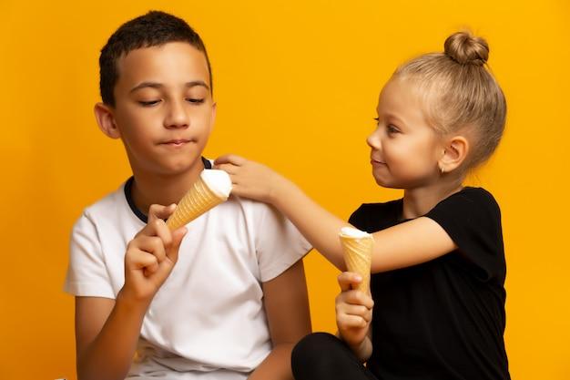 Glückliche geschwister, die eiscreme auf farbhintergrund essen