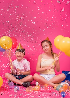 Glückliche geschwister, die party mit ballonen und konfetti über rosa hintergrund genießen