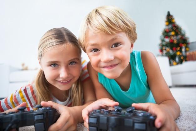Glückliche geschwister, die videospiele auf fußboden zur weihnachtszeit spielen