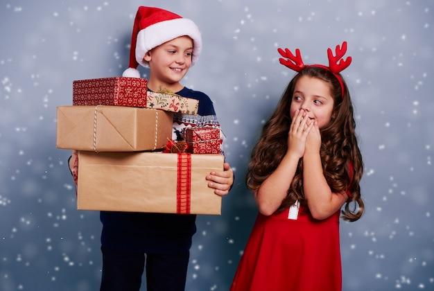 Glückliche geschwister mit stapel von geschenken unter schneefall