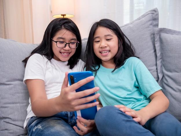 Glückliche geschwisterkinder, die auf dem sofa im wohnzimmer sitzen, sprechen mit den eltern auf dem handy zusammen, lächelndes älteres mädchen, das süße kleine schwester-videoanrufe per smartphone zeigt, sprechen mit der familie.