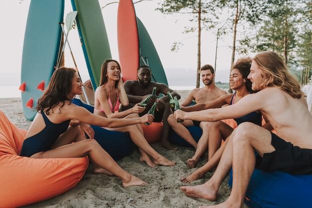 Glückliche gesellschaft, die auf osmanen legt. surfer-party.
