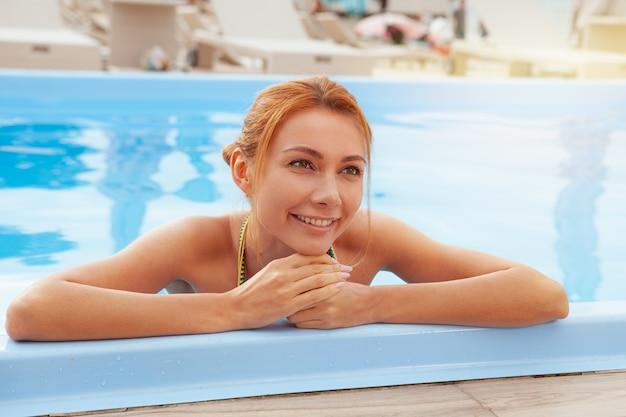 Glückliche gesunde frau, die am hotelpoolside sich entspannt
