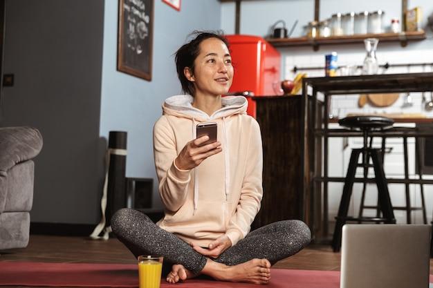 Glückliche gesunde frau, die auf einer fitnessmatte sitzt und am handy zu hause spricht