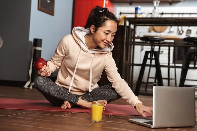 Glückliche gesunde frau, die auf einer fitnessmatte sitzt und laptop nach dem yoga-training zu hause verwendet