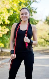 Glückliche gesunde frau mit einem springseil um ihren hals und einem fit formschönen körper, der auf einer straße in einem park steht