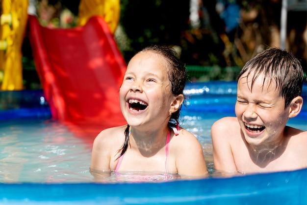 Glückliche gesunde kinder schwimmen im sommer im pool und lachen
