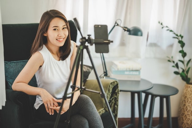 Glückliche gesunde lächelnde junge asiatische bloggerin, die die kamera anschaut, während sie das smartphone für die aufnahme von live-video-vlog zu hause verwendet using