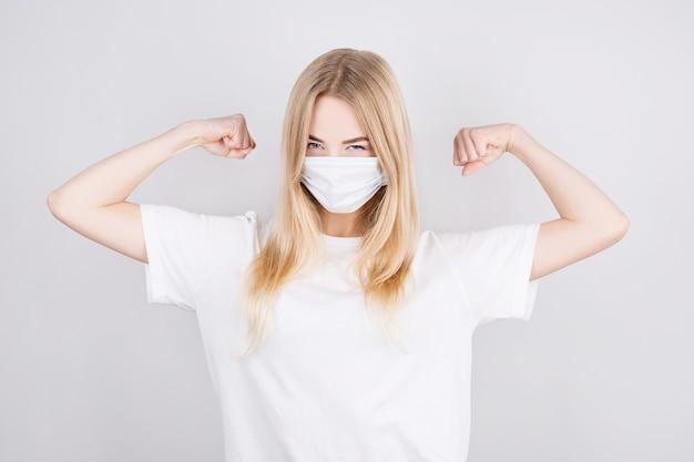 Glückliche gesunde starke junge blonde frau in einer medizinischen schutzmaske auf ihrem gesicht