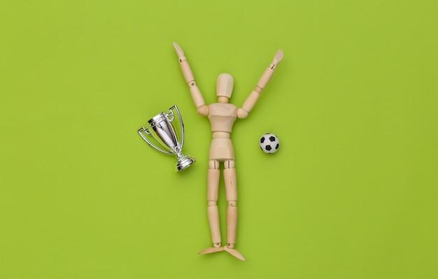 Glückliche gewinner-holzpuppe mit fußball und meisterschaftsbecher auf grünem hintergrund