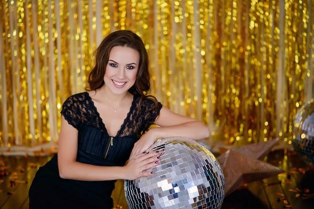 Glückliche glamouröse frau auf einer goldenen party mit discokugel. partymenschen