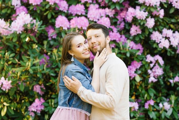 Glückliche glückliche junge paare in der liebe, die im frühjahr rhododendronblüte lächelt und genießt. valentinstag