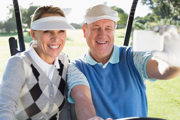 Glückliche golf spielende paare, die im golfbuggy nimmt ein selfie sitzen