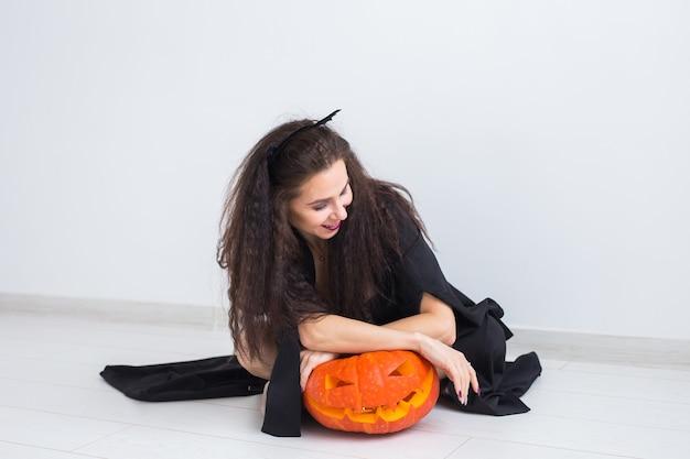 Glückliche gotische junge frau im hexen-halloween-kostüm, das über weiße raumoberfläche lächelt