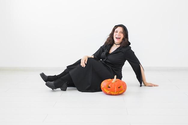 Glückliche gotische junge frau im hexen-halloween-kostüm, das über weiße raumwand lächelt.