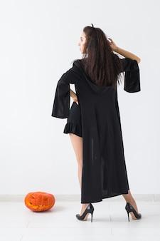 Glückliche gotische junge frau im hexenhalloween-kostüm, die über weißem raumhintergrund lächelt.