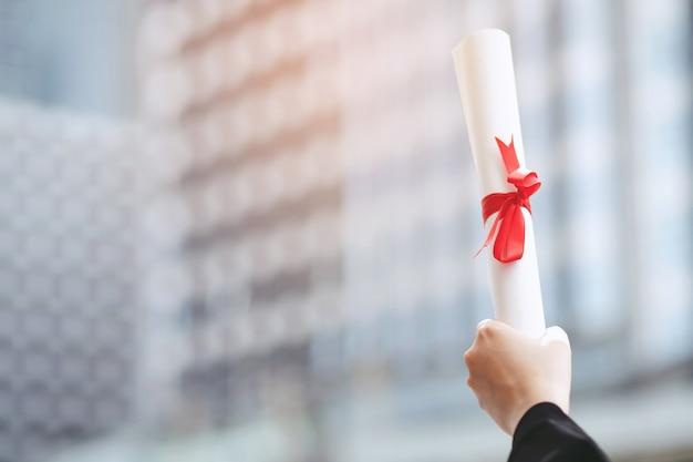 Glückliche graduierte junge frau tragen schwarzes kleid legte ihre hände hoch zertifikat. ein diplom mit rotem band mit schulgebäudehintergrund, bildungskonzept