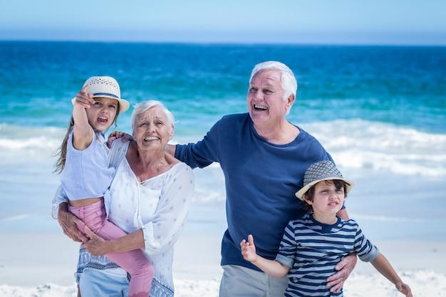 Glückliche großeltern, die den kindern doppelpol geben