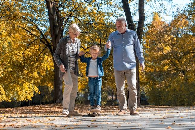 Glückliche großeltern, die mit ihrem enkel im park spielen