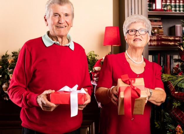 Glückliche großeltern hält weihnachtsgeschenke