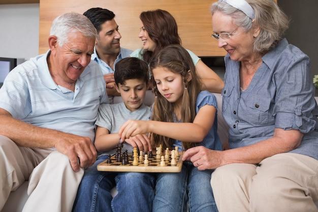 Glückliche großfamilie, die schach im wohnzimmer spielt