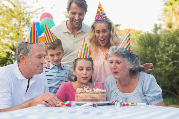 Glückliche großfamilie, die zusammen geburtstagskerzen ausbläst