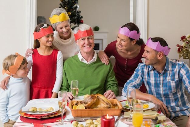 Glückliche großfamilie im partyhut am abendtisch