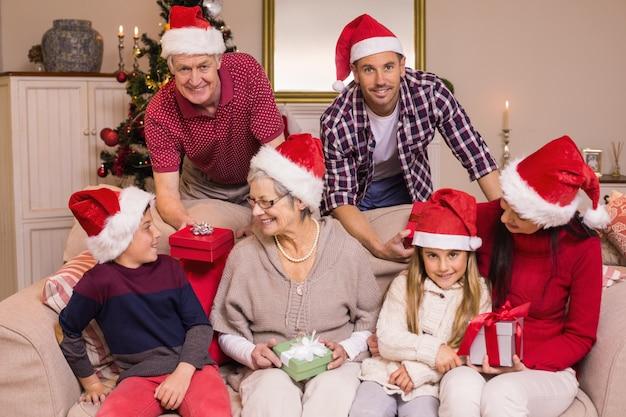 Glückliche großfamilie in sankt-hut, der geschenke hält