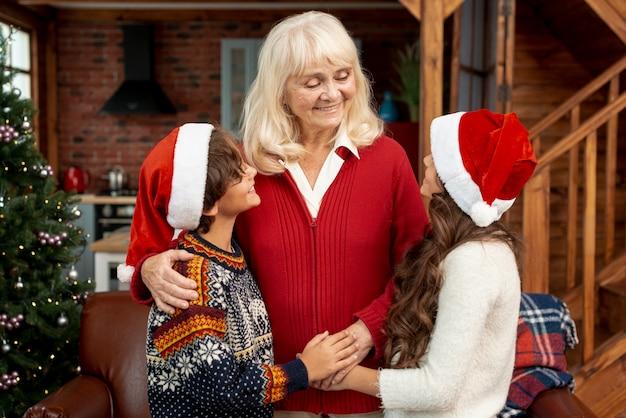 Glückliche großmutter des mittleren schusses, die enkelkinder betrachtet