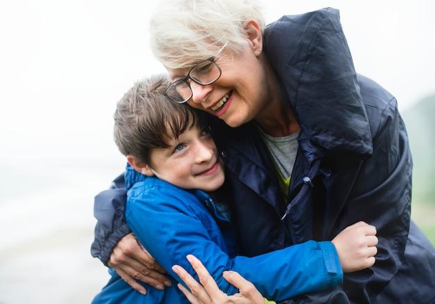 Glückliche großmutter, die ihren enkel umarmt