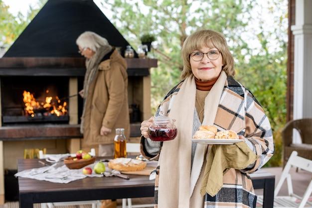 Glückliche großmutter mit brille und kariertem wollplaid-halteteller mit frischen leckeren hausgemachten brötchen und teekanne mit schwarzem tee