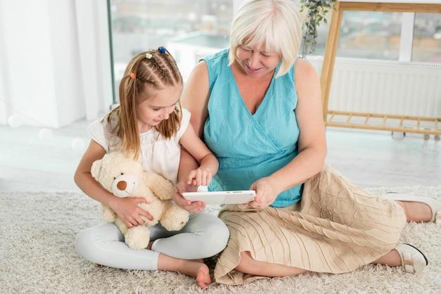 Glückliche großmutter mit enkelin mit tablette