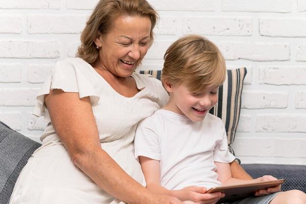 Glückliche großmutter und kind mit tablette