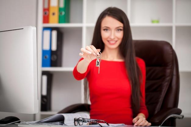Glückliche grundstücksmaklerfrau, die schlüssel zeigt.