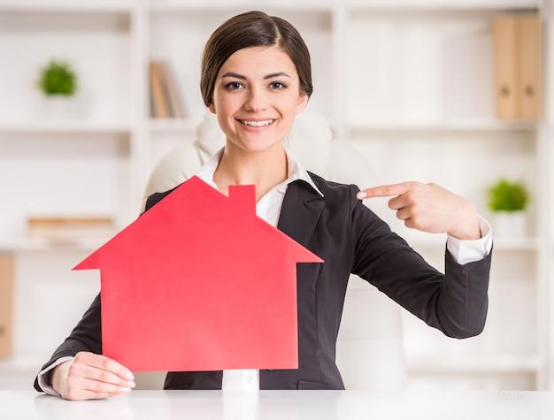 Glückliche grundstücksmaklerfrau zeigt nach hause für verkaufszeichen.