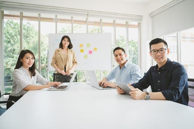 Glückliche gruppe junger asiatischer geschäftsleute während der brainstorming-konferenz für neues projekt. mann, der kamera betrachtet und lächelt.