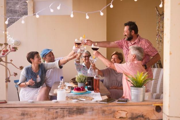 Glückliche gruppe unterschiedlichen alters, die zu hause oder im restaurant zusammen feiern und spaß in freundschaft haben