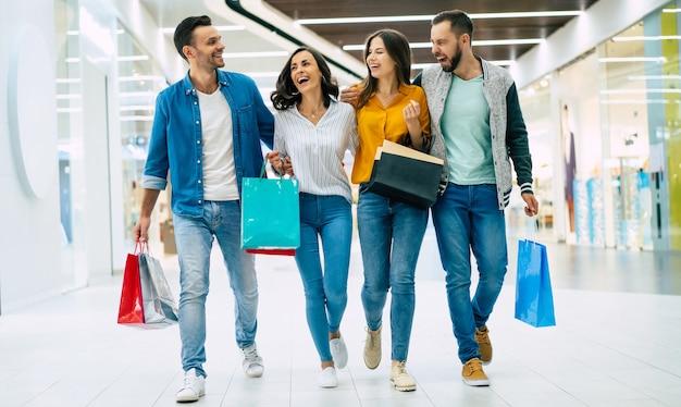 Glückliche gruppe von aufgeregten schönen modernen stilvollen freunden in freizeitkleidung mit papiertüten gehen im einkaufszentrum während des einkaufens spazieren.